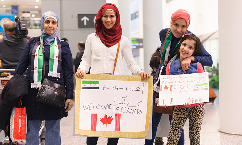 Family holding English and Arabic welcome signs for Syrian refugees at Toronto's Pearson International Airport.
